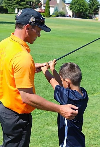 junior being instructed how to golf
